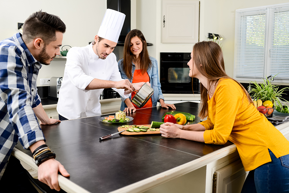 professional personal chef cook in customer's private kitchen house giving cooking lesson to young people at home